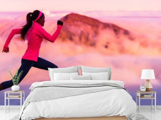 Trail runner nature landscape banner of running woman sports athlete on mountains background panorama crop in cold weather with pink clouds at sunset. Amazing scenic view of peaks in altitude.
