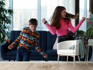 Couple of amazing teenage kids sister and brother dancing in living room into music enjoying entertainment vlogging online for follower broadcast making video.