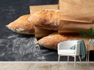 food, baking and cooking concept - close up of baguette bread in paper bags on table over dark background