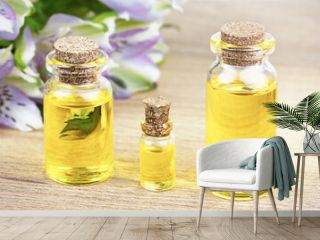 Bottles of essential oil with flowers on table. Alternative medical concept.