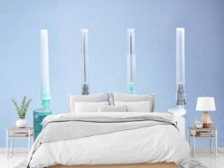 Row of different disposable syringes on blue background.