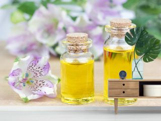 Glass bottles aroma oil and flowers on wooden table. Spa Treatment
