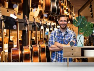 Portrait of professional seller standing in music shop and selling guitars instruments.