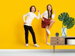 Full length body size photo of children dancing happy won lottery isolated bright yellow color background