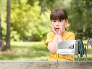 Amased little girl in a yellow t-shirt in a park