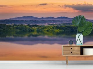Beautiful orange sunset scenery with green hills and mountains reflected in the water