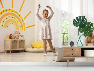 Cute little girl taking online dance class at home