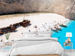 The beautiful Navagio shipwreck beach with turquoise sea and tourists enjoying the sea, Zakynthos island, Greece