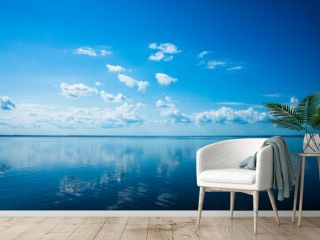 White fluffy clouds blue sky above a surface of the sea. Beautiful sky and ocean using for background. The sky is reflected in the water. Copy space.
