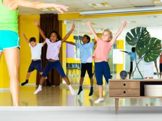 happy sportive children with female teacher training in modern dance hall, jumping together