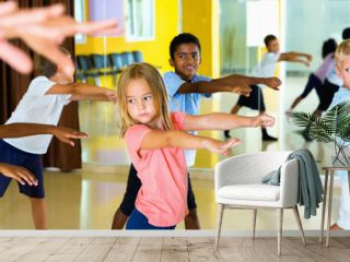 Happy positive smiling preteen boys and girls practicing dance, stretching with female trainer in dance hall