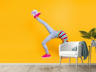 Photo of sportive girl stay arms leg hold present box wear striped shirt jeans footwear isolated yellow color background