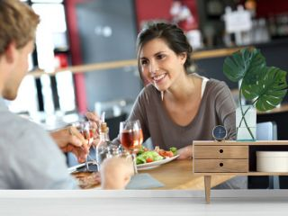 Young woman in restaurant eating lunch with boyfriend