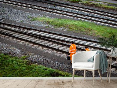 Two workers walking along railroad tracks