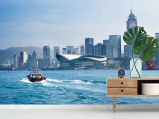 Red tug boat in front of Hong Kong skyline and panorama cityscape