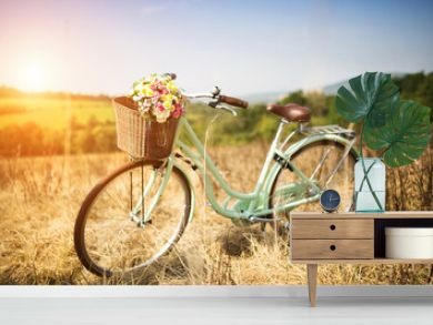 Vintage bicycle with basket full of flowers standing in field