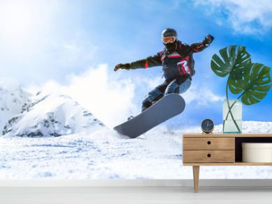Jumping snowboarder from hill in winter