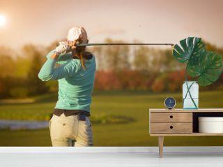 Woman golf player hitting ball.
