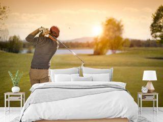 Male golf player swinging golf club at dusk.