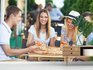 Group of cheerful teenage friends sharing pizza in a outdoor cafe