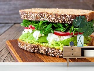 Superfood sandwich with whole grain bread, avocado, egg whites, radishes and pea shoots on wood board