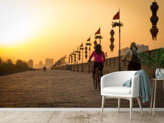 XIAN, CHINA - MARCH 13 2016: People ride bicycle on City Wall of  Xi'an famous Historic Sites in china sunset in the evening