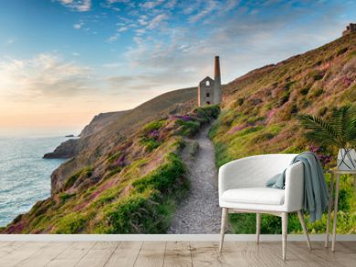 Hazy summer evening on the South West Coast Path as it approaches the ruins of the Wheal Coates mining engine house near St Agnes in Cornwall