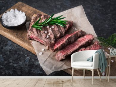 Grilled beef steak with rosemary and salt on cutting board