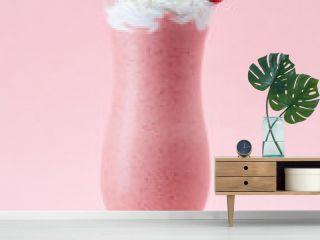 Glass of strawberry milkshake with whipped cream and fresh straw