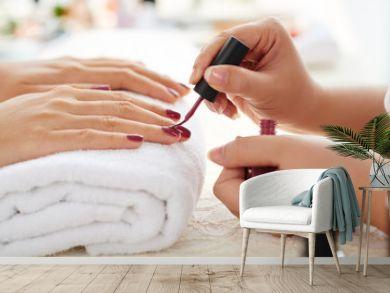 Side view of manicurist applying marsala nail polish