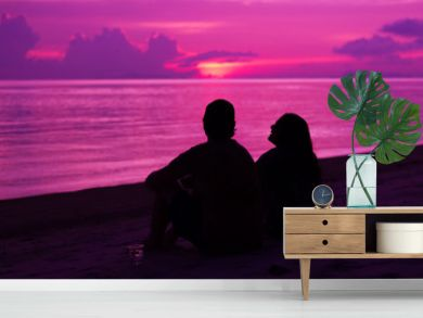 Silhouette of the couple enjoying the sunset on the beach