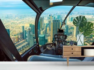 Helicopter cockpit flies in skyscrapers of Dubai downtown skyline on Sheikh Zayed Road, United Arab Emirates, with pilot arm and control board inside the cabin.