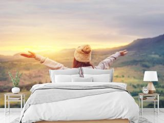 Carefree Happy Woman Enjoying Nature on top of mountain cliff with sunrise. Beauty Girl Outdoor. Freedom concept. Sunbeams. Enjoyment.
