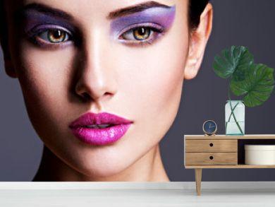 Beautiful girl's face closeup with purple eye make-up. fashion m