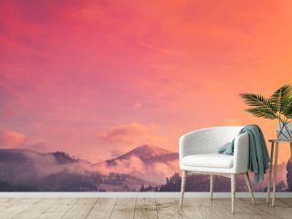 Majestic foggy forest and mountain peak. Dramatic and picturesque sunrise pink orange sky. Carpathians, Ukraine, Europe. Beauty worldmountain landscape. Exploring beauty world. Travel background.