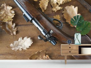 hunting carbine and oak leaves on wooden background top view