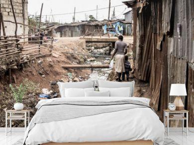 People walking along an open sewer in a slum in Africa
