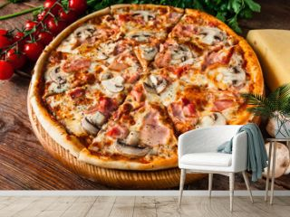 Traditional italian pizza with ham and mushrooms, served on rustic wooden table with cherries, cheese, parsley and peppercorns. Restaurant menu photo.