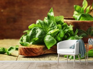 Fresh green basil in olive mortar with pestle, vintage wooden background, rustic style, selective focus