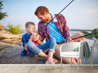 Portrait of playful handsome father tickling son sitting on rock by lake while enjoying fishing together and laughing in rays of sunset sunlight