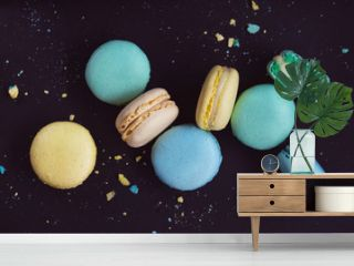 Macaroons on dark background, colorful french cookies macarons. The broken macarons with crumbs