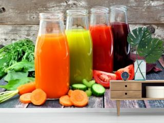 Four bottles of healthy vegetable juice with scattered vegetables and a rustic wood background