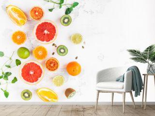 Fruit background. Colorful fresh fruit on white table. Orange, tangerine, lime, kiwi, grapefruit. Flat lay, top view, copy space