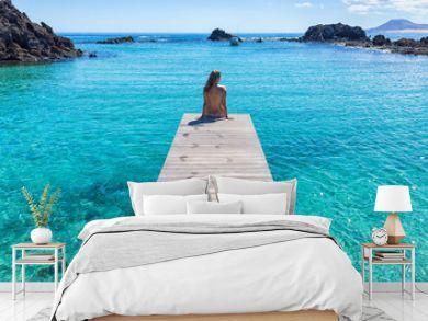 Spain, Canary Islands, Fuerteventura, Isla de lobos. Topless girl on a pier clear transparent water