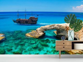 Pirate ship sailing near famous rock arch on Cavo Greko peninsula, Cyprus island