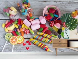 Lollipops and sweet candies of various colors on wooden background