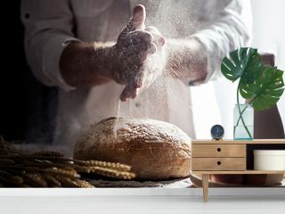 Man sprinkling flour over freshly baked bread on kitchen table