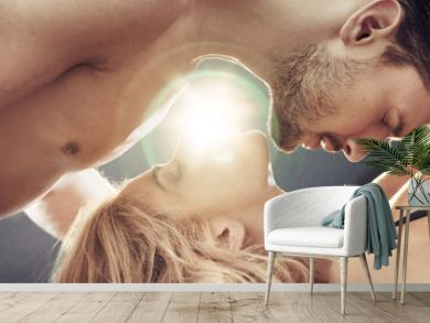Conceptual portrait of a sensual, nude couple in the bedroom