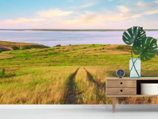 Scenic sea view from top of hills. Beautiful summer background. Amazing landscape with yellow meadows, green trees, blue sky, steep cliffs and picturesque bay. Panoramic photo. Camping, rest, relax.