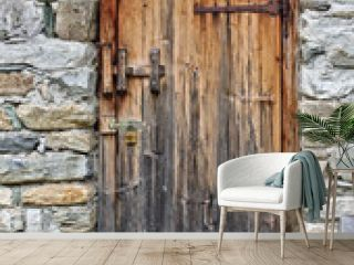 Old wooden door in field stone wall with rusty hinges and padlock